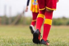 Badine le football du football - jambes de footballeurs avec l'espadrille du football Photos stock
