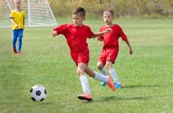 Badine le football du football - les joueurs d'enfants sont assortis sur le terrain de football Photographie stock