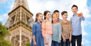 Badine le selfie parlant de smartphone au-dessus de Tour Eiffel Photo stock