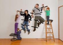 Badine le travail d'équipe attachant du ruban adhésif à des parents pour murer Photos libres de droits
