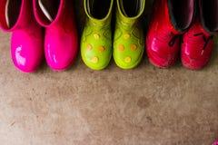Badine rose lumineux, rouge, les bottes en caoutchouc de vert, faisant du jardinage, bottes Mode de jour pluvieux Chaussures en c photos stock