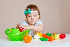 Badinez avoir une table complètement de nourriture en plastique Enfant en bas âge gai mangeant de la salade et des fruits sains Photo libre de droits