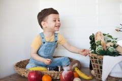 Badinez avoir une table compl?tement d'aliment biologique Enfant en bas ?ge gai mangeant de la salade et des fruits sains B?b? ch photo stock