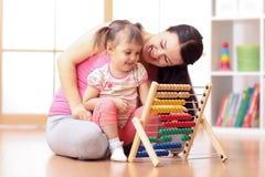 Badinez et enfantez jouer avec l'intérieur d'abaque à la maison Images libres de droits