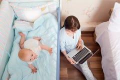 Badinez jouer dans le lit, travaux de pyjamas de maman avec l'ordinateur portable que j'ai obtenu des clos photos libres de droits