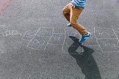 Badinez jouer le jeu de marelle sur le terrain de jeu, activités en plein air d'enfants Image libre de droits