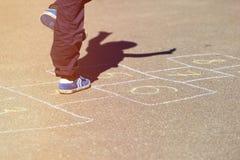 Badinez jouer le jeu de marelle sur le terrain de jeu, activités en plein air d'enfants Image stock