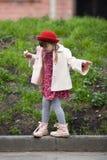 Badinez la fille avec des tresses dans le chapeau mangeant la crème glacée et les promenades  Image libre de droits