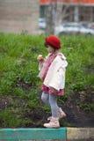 Badinez la fille avec des tresses dans le chapeau mangeant la crème glacée et les promenades  Image stock