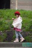 Badinez la fille avec des tresses dans le chapeau mangeant la crème glacée et les promenades  Photographie stock