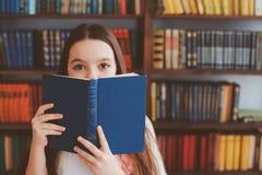 badinez la fille d'école dans la bibliothèque se cachant derrière le livre Photo libre de droits