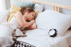 Badinez la fille dormant dans le début de la matinée dans le lit avec le réveil images stock