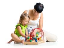 Badinez la fille et la mère jouant avec le jouet éducatif de couleur Photographie stock libre de droits