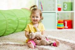 Badinez la fille jouant et étreignant le chaton affectueux d'animal familier Photo stock