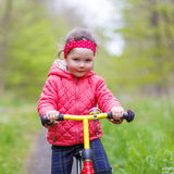Badinez la fille montant son premier vélo, dehors Images stock