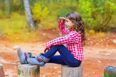 Badinez la fille s'asseyant dans le joncteur réseau de forêt semblant lointain Images stock
