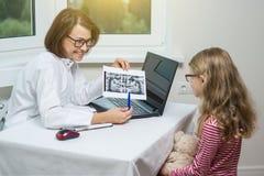 Badinez la fille sur la consultation avec le dentiste, semblant le rayon X dentaire photo libre de droits