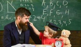 Badinez la gêne gaie tout en étudiant, déficit d'attention Concept vilain d'enfant Le père avec la barbe, professeur enseigne photo libre de droits