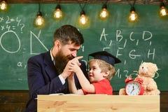 Badinez la gêne gaie tout en étudiant, déficit d'attention Engendrez avec la barbe, professeur enseigne le fils, petit garçon pro photographie stock libre de droits
