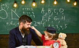 Badinez la gêne gaie tout en étudiant, déficit d'attention Engendrez avec la barbe, professeur enseigne le fils, petit garçon pro photographie stock