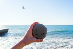 Badinez la main du ` s tenant une pierre avec le visage de sourire à côté de la mer dans le jour ensoleillé Images stock