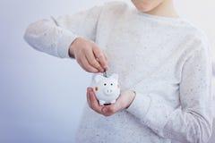 Badinez la main mettant la pièce de monnaie dans la tirelire ou la tirelire Images stock