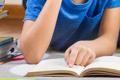 Badinez la main sur le livre tandis que des livres de lecture photographie stock
