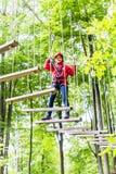 Badinez la marche sur le pont de corde dans le cours s'élevant Images stock