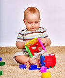 Badinez le bébé garçon maniant habilement avec le jouet de puzzle sur le plancher Photos libres de droits