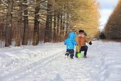 Badinez le fonctionnement en parc d'hiver et ayez l'amusement avec la famille photos stock