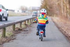 Badinez le garçon dans le casque de sécurité et le vélo coloré d'équitation d'imperméable, outd Photo libre de droits