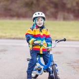 Badinez le garçon dans le casque de sécurité et le vélo coloré d'équitation d'imperméable, outd Photographie stock