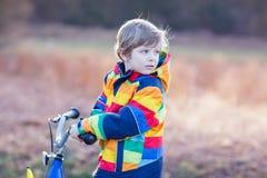 Badinez le garçon dans le casque de sécurité et le vélo coloré d'équitation d'imperméable, outd Photos libres de droits