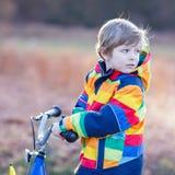 Badinez le garçon dans le casque de sécurité et le vélo coloré d'équitation d'imperméable, outd Photographie stock libre de droits