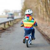 Badinez le garçon dans le casque de sécurité et le vélo coloré d'équitation d'imperméable, outd Images stock