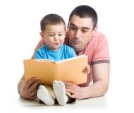 Badinez le garçon et le père a lu un livre sur le plancher à la maison Photo stock
