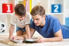 Badinez le garçon et son papa a lu un livre Photos libres de droits