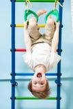 Badinez le garçon sur les anneaux gymnastiques dans la classe de gymnase Images stock