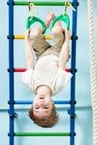 Badinez le garçon sur les anneaux gymnastiques dans la classe de gymnase Image stock