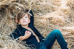 Badinez le garçon tenant la feuille et les mensonges d'or sur le foin Vente pour la collection entière d'automne, remises et merv photos stock