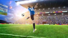 Badinez le joueur de football frappant la boule sur un stade de football Photos stock