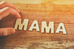 Badinez le mot MAMAN d'orthographe de main faite avec les lettres en bois de bloc sur le fond en bois vintage filtré et modifié l Photographie stock libre de droits