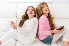 Badinez les filles ayant l'amusement jouant de nouveau au dos avec le PC de comprimé sur le sofa Images stock