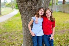 Badinez les filles d'ami chuchotant l'oreille jouant dans un arbre de parc Photo stock