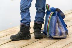 Badinez les jambes et le sac à dos de garçon sur un pilier en bois Photographie stock