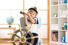 Badinez les jeux de capitaine habillés par garçon ou de marin sur la chaise en tant que bateau dans sa chambre L'enfant regarde p Photos stock