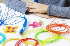Badinez les mains et 3d le stylo, filaments colorés sur le bureau blanc Photographie stock libre de droits