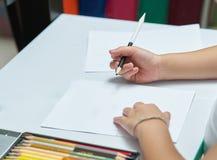 Badinez les mains tient le crayon de couleur et pense aux choses d'écriture sur W photos stock