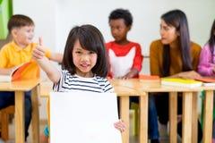 Badinez les pouces de fille et en tenant l'affiche blanche vide avec la diversité Image libre de droits
