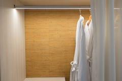 Badjassen die in garderobe bruine badjas hangen Stock Foto's